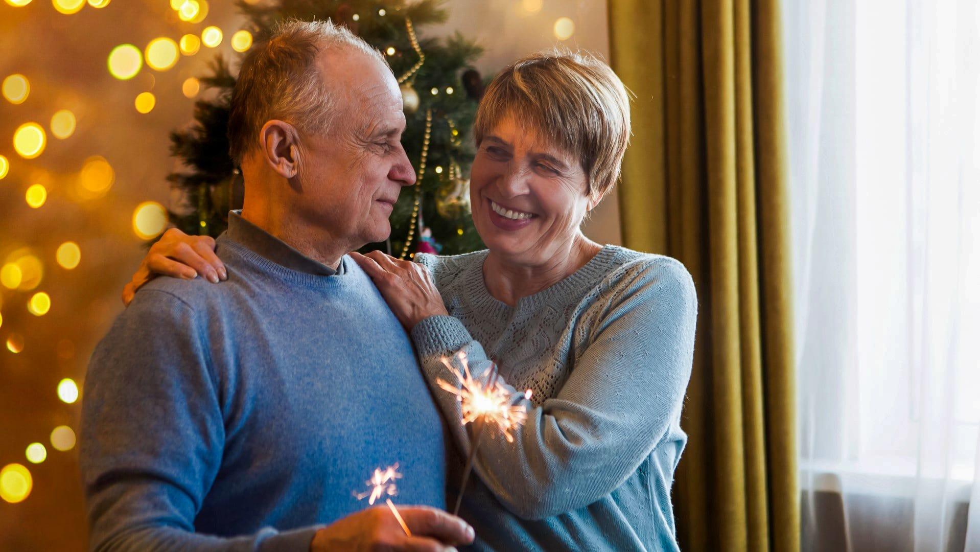 Elderly senior couple on new years eve with sparkler and christmas tree