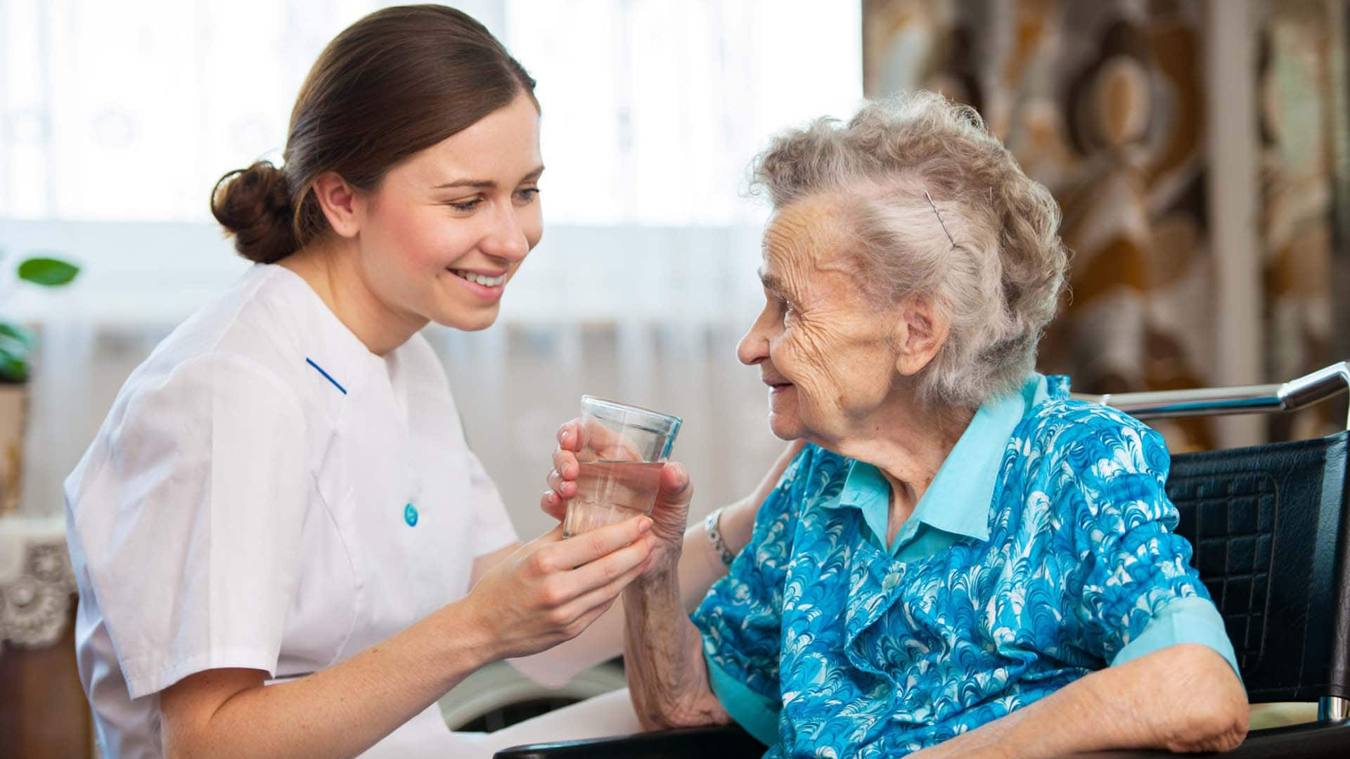 caregiver giving water to client during home care in-home services